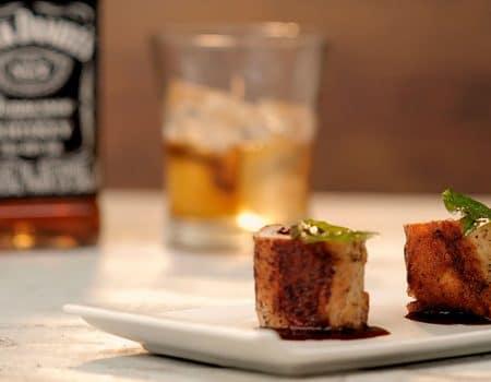 Rollos de cerdo rellenos con queso provolone y arándanos, en salsa para teriyaki y whiskey
