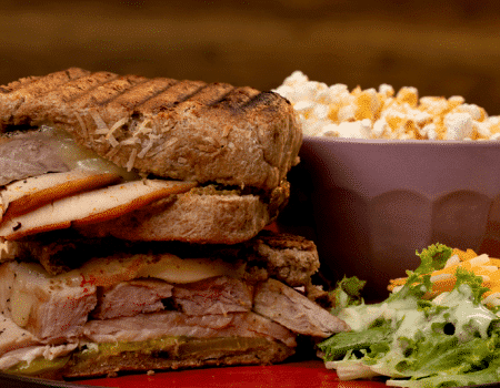 Panini de cerdo, jamón de pavo y queso, acompañado de palomitas de maíz con caramelo